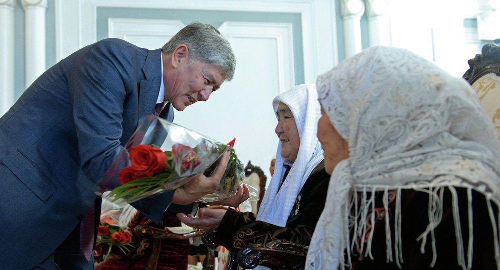 Президент Алмазбек Атамбаев награждает многодетную мать. Архивное фото
