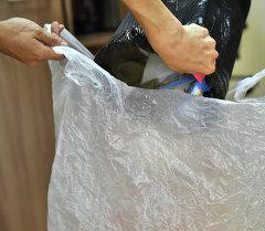 Выбрасывание мусора в пакеты. Архивное фото