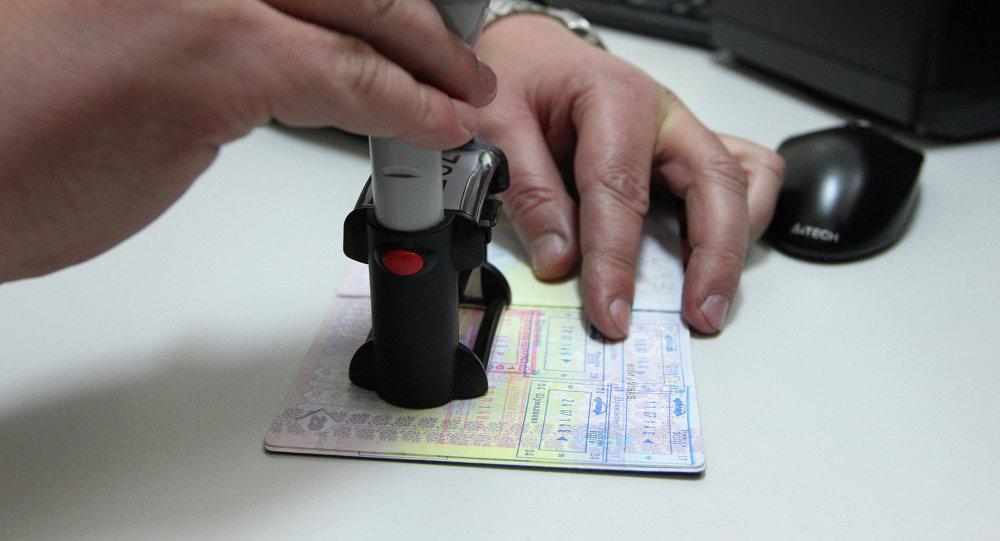 Сотрудник ставит печать на паспорт. Архивное фото