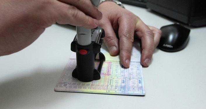 Сотрудник пограничной службы ставит в паспорт штамп. Архивное фото