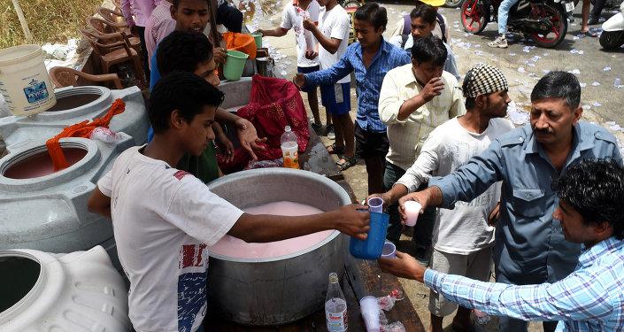 Индийские добровольцы распространяют бесплатную холодную пресную воду на улице в Нью-Дели.