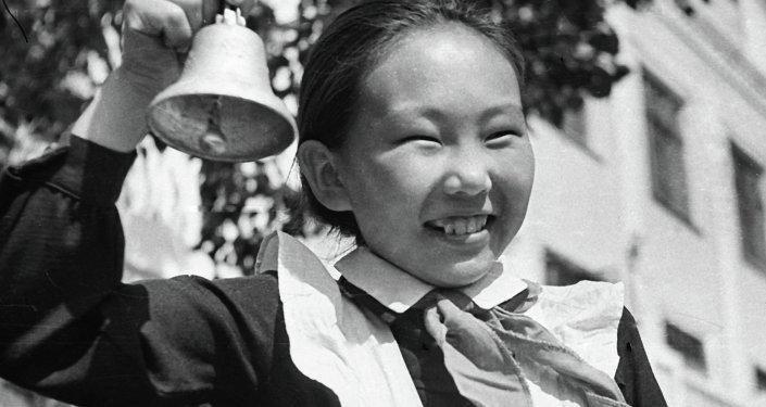Пионерка в парадной форме звонит в колокольчик на последнем школьном звонке