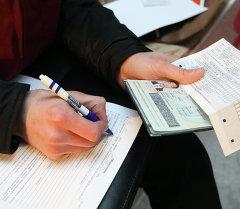 Сотрудник федеральной миграционной службы Новосибирской области проводит проверку документов. Архивное фото