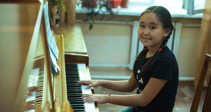 Пианинодо ойногон кыз. Архивдик сүрөт