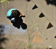 Ребенок рисует на асфальте. Архивное фото