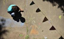 Мальчик рисует на асфальте. Архивное фото