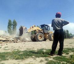 Работники мэрии города Бишкека сносят бульдозером незаконно построенные дома