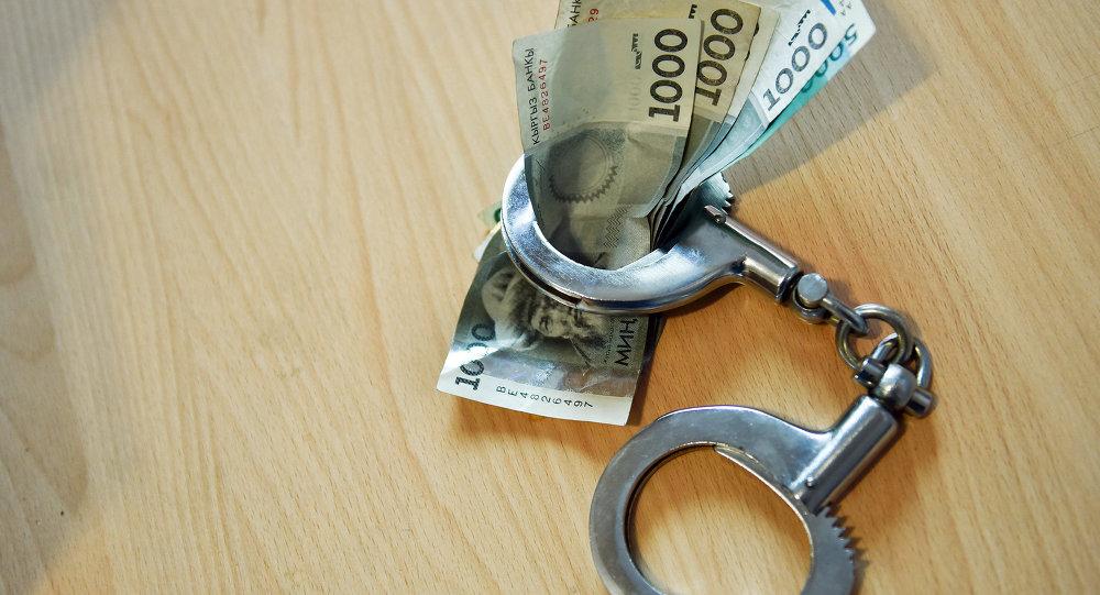 Наручники с деньгами на столе. Архивное фото