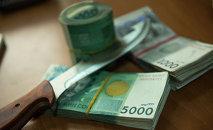 Пачка кыргызских валют и нож. Архивное фото
