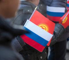 Архивное фото молодых людей, которые держат флаг Кыргызстана и России