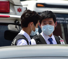 Түштүк Кореялык оорукананын маскачан сакчылары Сеул Улуттук госпиталдын алдында. Архив