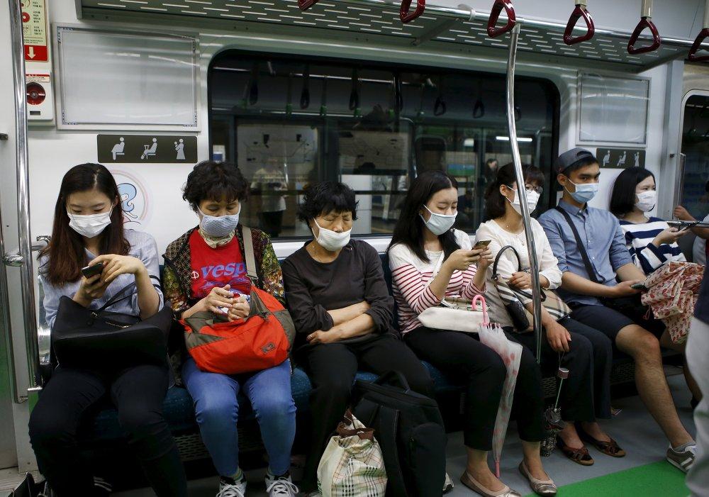 Пассажиры в метро Сеула в медицинских масках
