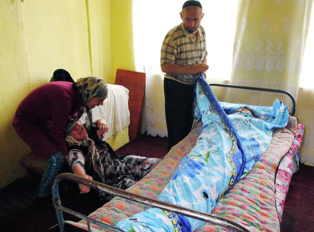 Уулунун сөөгүн коёр алдында ыйлап турган эне, Ош шаары, 17-июнь, 2010