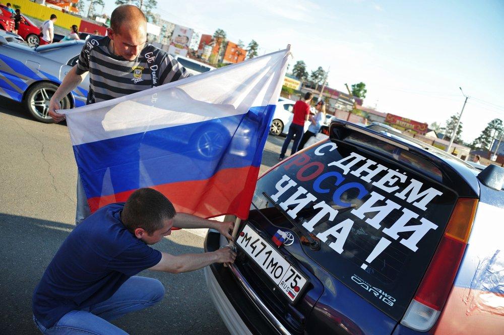Спортивные и культурные мероприятия, приуроченные к празднованию Дня России, прошли в Чите и 20 районах Забайкалья. На фото: автолюбители устанавливают флаг России на автомобиль перед пробегом, приуроченным к празднованию Дня России, в Чите.