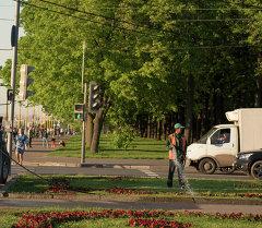 Сотрудник службы поливает цветы в городе Москве. Архивное фото