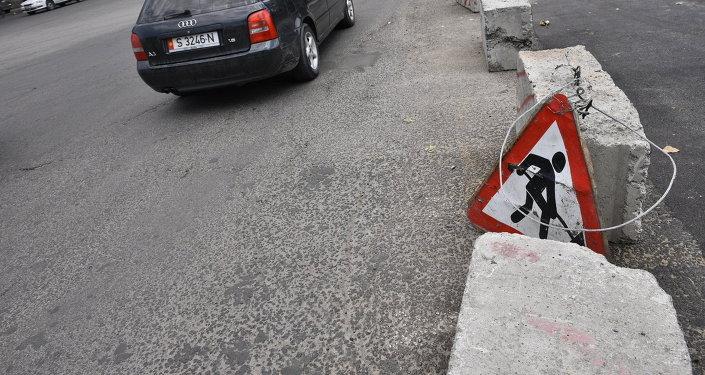 Знак дорожные работы возле дороги. Архивное фото