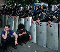 Демонстранты сидят на улице перед сотрудниками ОМОНа во время акции протеста против повышения цен на электроэнергию в столице Армении Ереване 24 июня 2015 года.  Архивное фото
