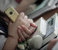 Ученица с телефоном. Архивное фото