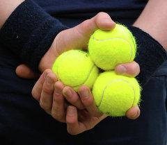 Юноша держит в руках теннисные мячи. Архивное фото