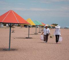 Продавщицы рыбы и кукурузы идут по пляжу Иссык-Куля. Архивное фото