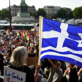 Протестующий держит греческий флаг, которая принимает участие в митинге в поддержку народа Греции на площади Бастилии в Париже. Архивное фото