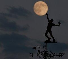 Луна поднимается над флюгером здания Всеанглийского клуба лаун-тенниса и крокета, где проходит знаменитый Уимблдонский теннисный турнир. Лондон, 30 июня 2015 г. В течение месяца мы увидим полную Луну дважды.