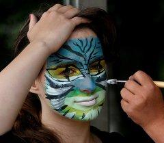 Девушке делают рисунок на лице. Архивное фото
