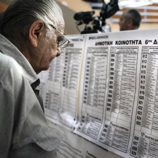 Мужчина рассматривает списки адресов центров для голосования на референдуме в Греции. Архивное фото