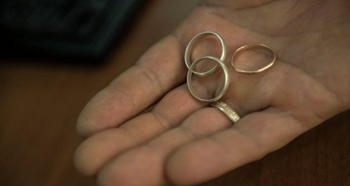 Кольца молодоженов в руке. Архивное фото