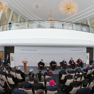 Президент Российской Федерации Владимир Путин (в центре на дальнем плане) на встрече лидеров БРИКС с членами Делового совета БРИКС в Уфе. Архивное фото