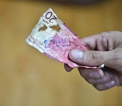 Старые дырявые деньги в руках человека. Архивное фото