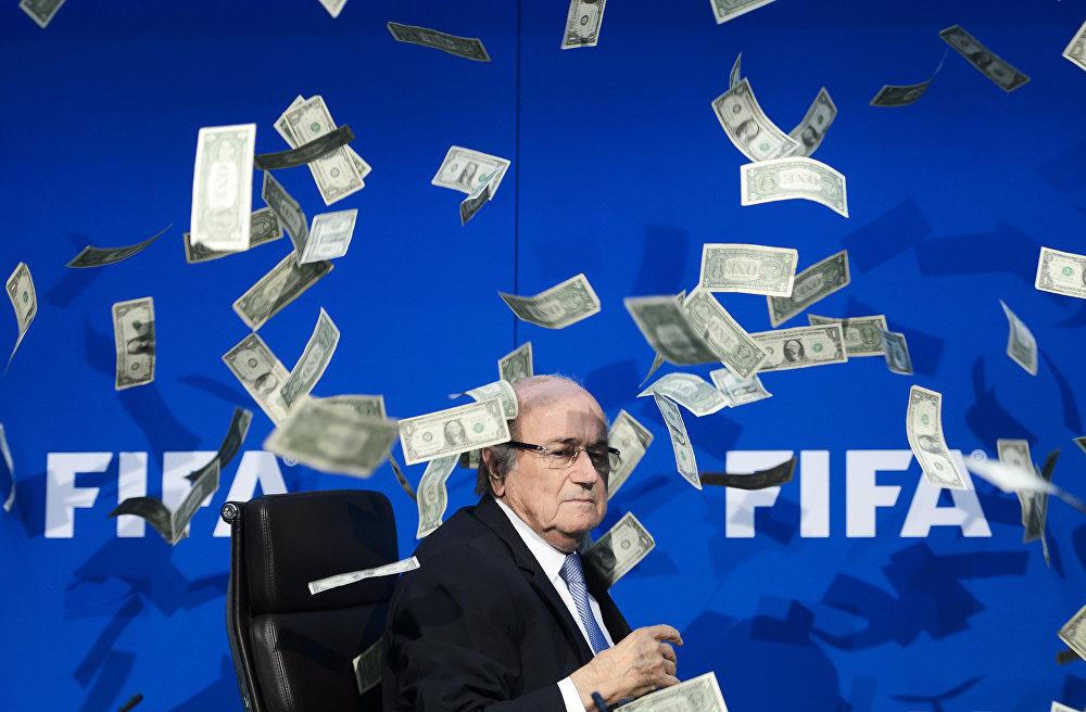 ФИФАнын башчысы Йозеф Блаттер Цюрихтеги маалымат жыйында, 20-июль. Британиялык куудул Саймон Бродкин (лакап аты Ли Нельсон) Блаттер отурган жерге жакындап Бул сага 2026-жылы Түндүк Кореяда дүйнөлүк чемпионатты өткөрүү үчүн акчаны ыргыткан