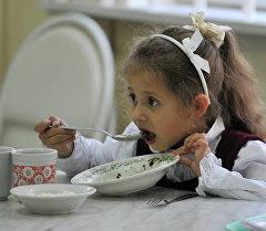 Архивное фото ребенка, который обедает в школьной столовой