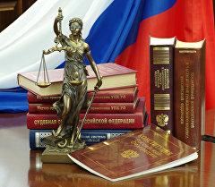 Статуя Фемиды и юридическая литература на столе. Архивное фото