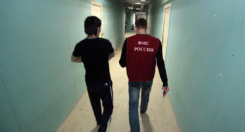 Иностранный рабочий идет по коридору общежития вместе с сотрудником отдела иммиграционного контроля Управления Федеральной Миграционной Службы (УФМС) России. Архивное фото