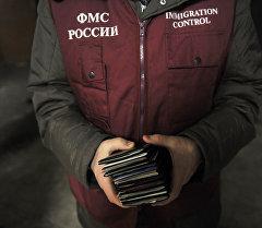 Сотрудник ФМС держит в руках паспорта задержанных во время рейда Федеральной миграционной службы. Архивное фото