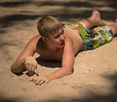 Мальчик загорает у пляжа. Архивное фото