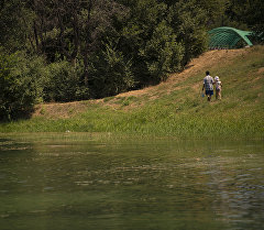 Мужчина с ребенком у озера. Архивное фото