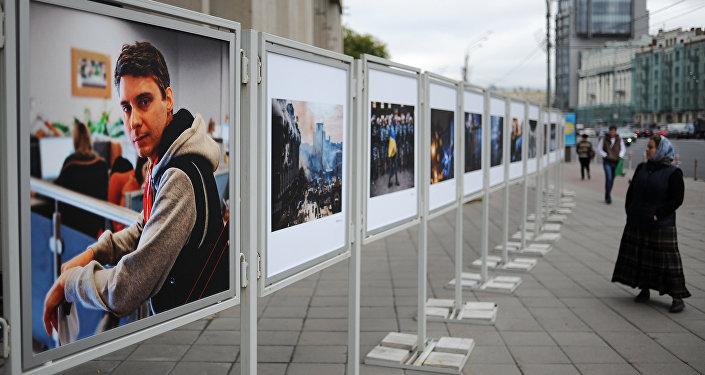 Жительница Москвы рассматривает работы погибшего на Украине фотокорреспондента Андрея Стенина у здания МИА Россия сегодня. Архивное фото