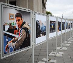 Жительница Москвы рассматривает работы погибшего на Украине фотокорреспондента Андрея Стенина у здания МИА Россия сегодня.