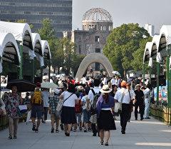 Жители Японии идут на мемориальный памятник посвященный жертвам бомбардировки в Хиросиме.