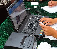 Проверка данных гражданина во время сбора биометрических данных. Архивное фото