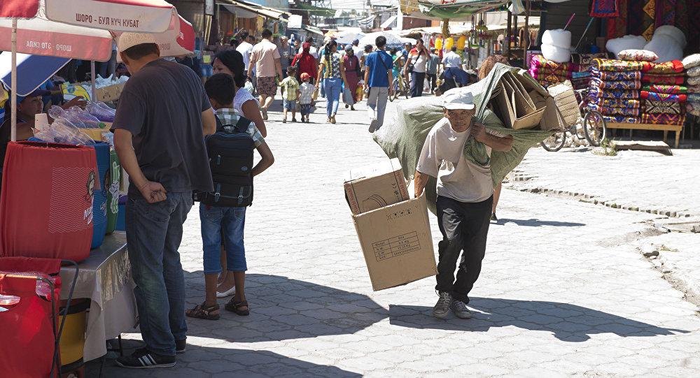 Человек собирающий пустые коробки на рынке Дордой. Архивное фото