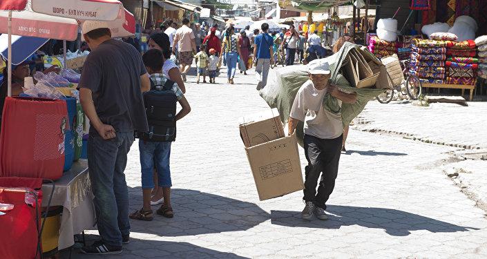 Мужчина переносит бумажные картоны на рынке Дордой, Бишкек. Архивное фото