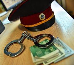 Милиционердин фуражкасы, акча жана кол кишен. Архив