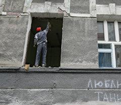 Рабочий демонтирует старые оконные рамы в здании. Архивное фото