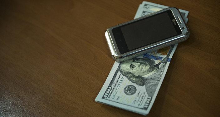 Мобильный телефон и сто долларовые купюры. Архивное фото