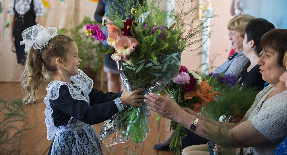 Первоклассница дарит цветы учительнице. Архивное фото