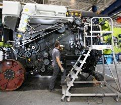 Рабочий в цехе занимается сборкой зерноуборочного комбайна на заводе. Архивное фото