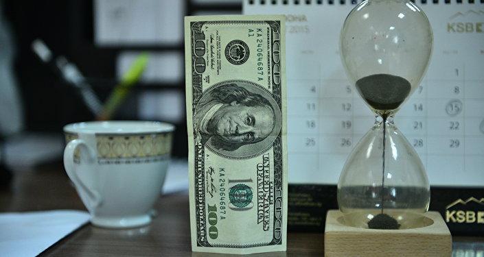 Сто долларовая купюра песочные часы на столе. Архивное фото